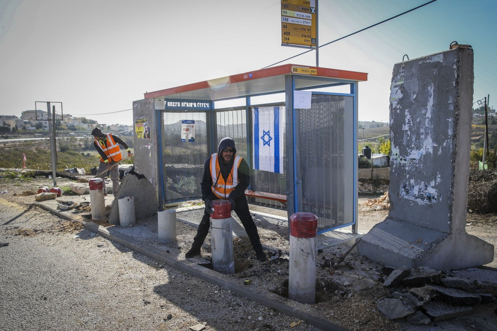 Placing bus stop barriers at the entrance to Alon Shvut after a Palestinian killed a young Jewish woman and injured two more, November 11, 2014. (Nati Shohat/Flash90)