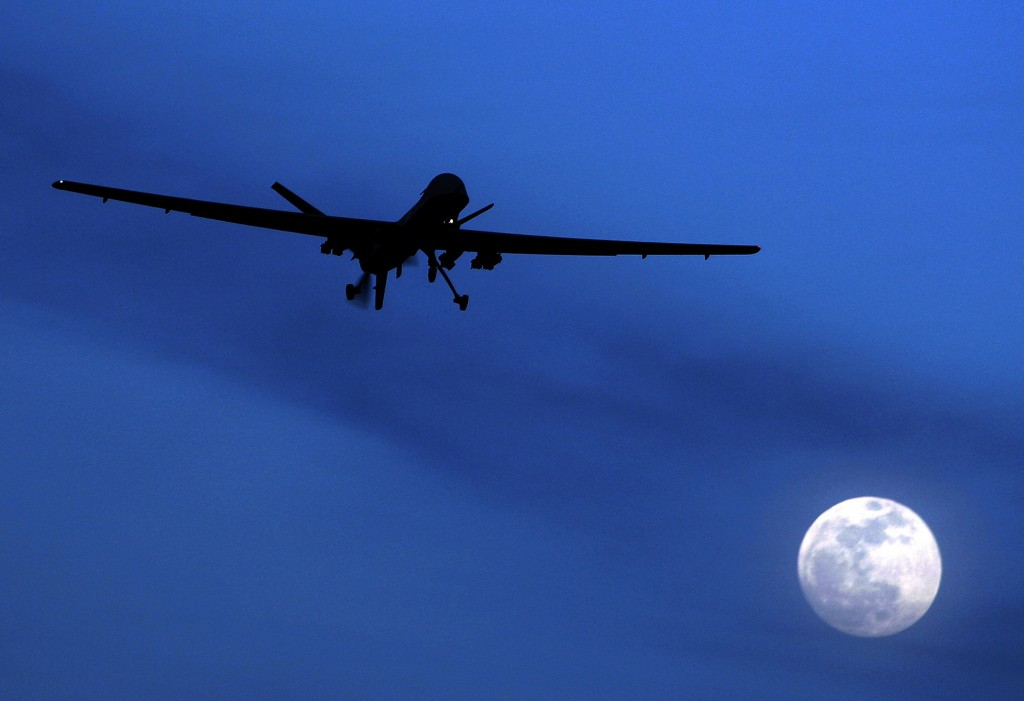 FILE - In this Jan. 31, 2010 file photo, an unmanned U.S. Predator drone flies over Kandahar Air Field, southern Afghanistan, on a moon-lit night. (AP Photo/Kirsty Wigglesworth, File)