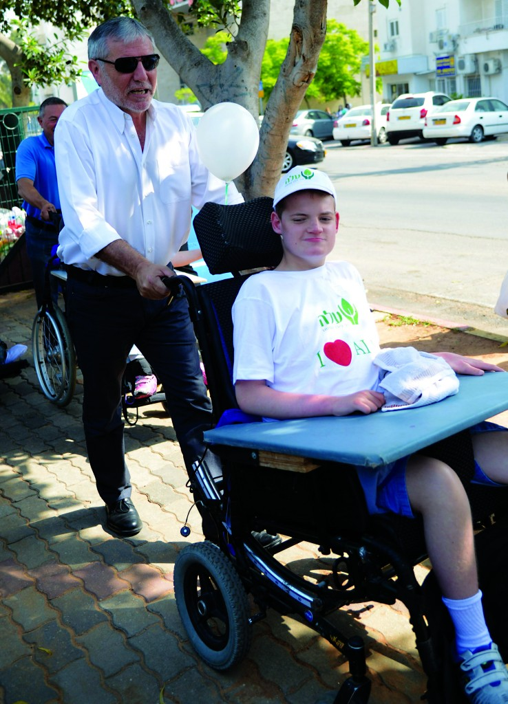 A youth in a wheelchair is pushed by Minister of Social Affairs Meir Cohen during a march with disabled Israelis in the city of Gadera, in 2013. (Yossi Zeliger/FLASH90)