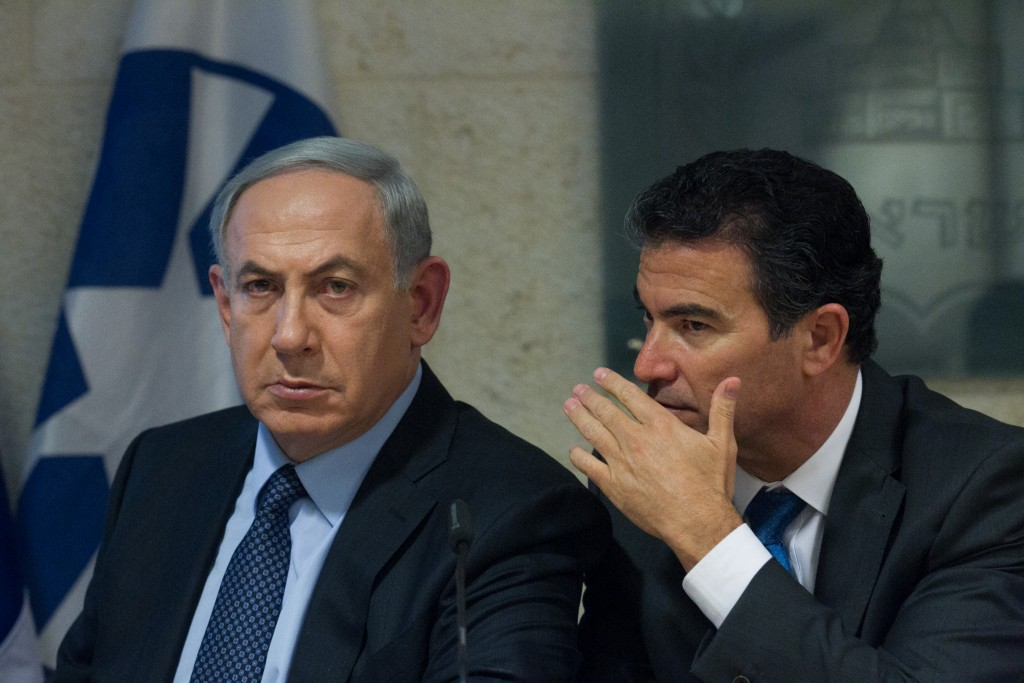 Yossi Cohen, head of the national security council, whispers into the ear of Prime Minister and Minister of Foreign Affairs Binyamin Netanyahu at an October press conference at the Foreign Ministry in Jerusalem regarding the recent wave of terror attacks in Israel. (Photo by Miriam Alster/Flash90)