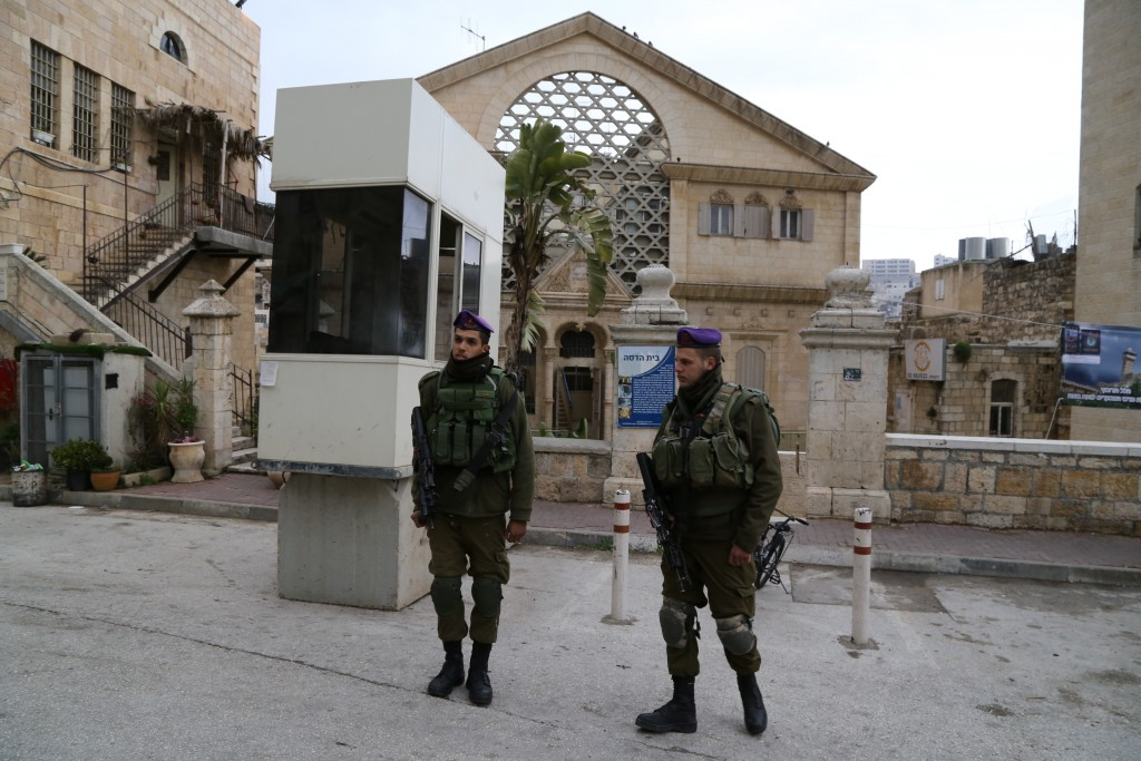 Israeli security forces stand guard next to Hadassah House (Beit Hadassah) in Hebron in the West Bank on December 13, 2015. Photo by Gershon Elinson/Flash90