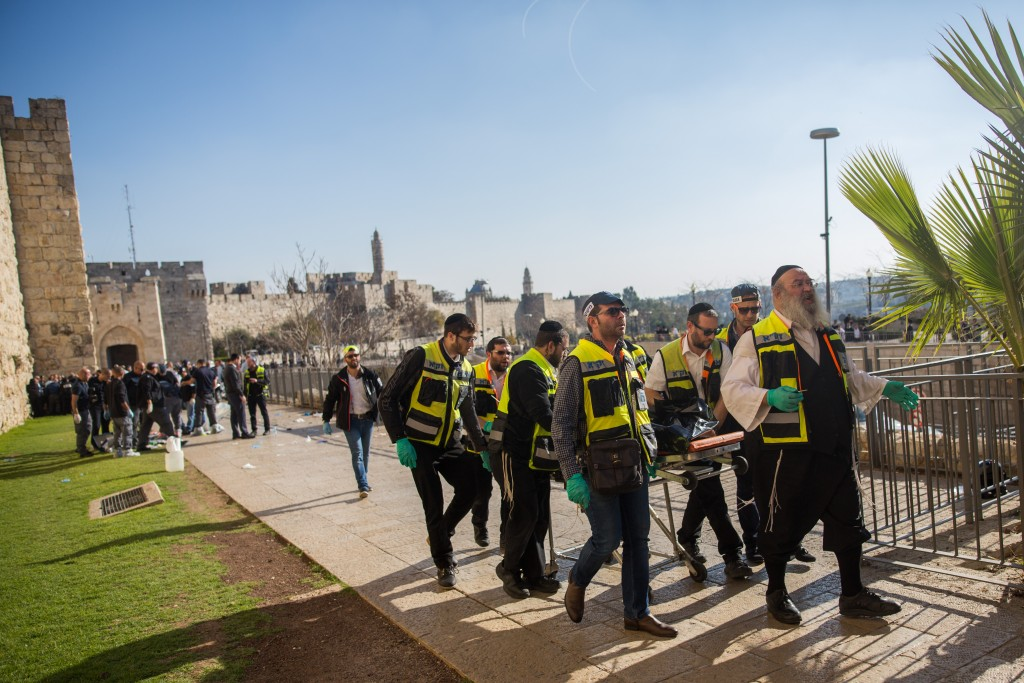 Zaka volunteers and Israeli security personnel at the scene of Wednesday's stabbing attack. (Yonatan Sindel/Flash90)