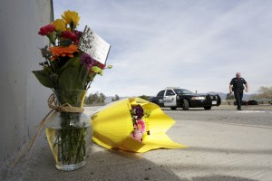 A San Bernardino police officer stands near flowers left near the scene of Wedneday's shooting rampage, at the Inland Regional Center, in San Bernardino, California December 3, 2015. (Reuters/Jonathan Alcorn)