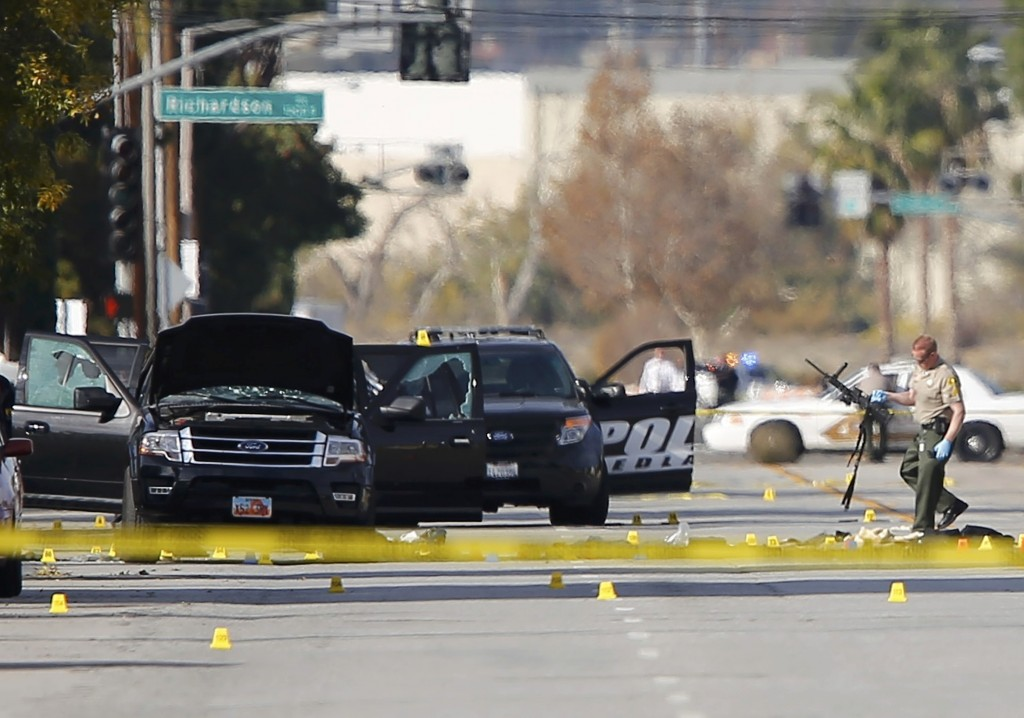 A police officer picks up a weapon from the scene of the investigation around the area of the SUV where the two suspects were shot by police following Wednesday's mass shooting. (Reuters/Mike Blake)