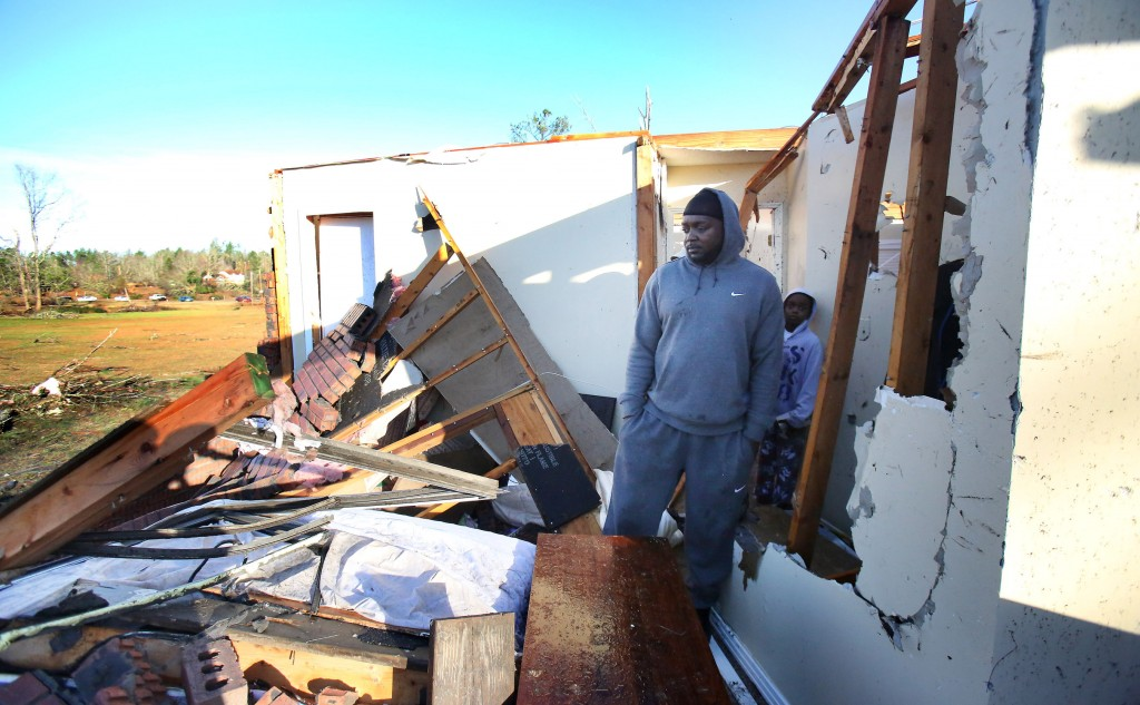 A family inspects the tornado damage to their home in Holly Springs, Miss. (Stan Carroll/The Commercial Appeal via AP)