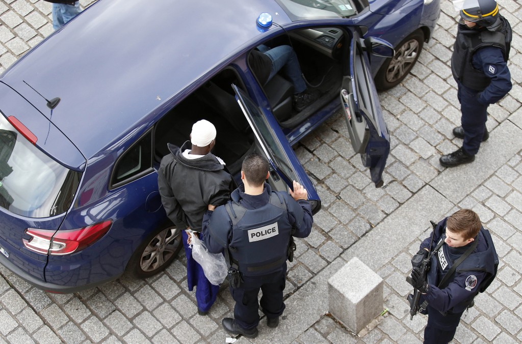 Police officers arrest a man in Saint-Denis, a northern suburb of Paris, Wednesday, Nov. 18, 2015. Officials say seven people have been arrested in a raid on an apartment building where suspects in last week's Paris attacks were holed up. Authorities believe there may still be someone hiding in an apartment. (AP Photo/Francois Mori)