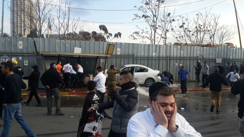 Security personnel at the scene of the car ramming attack in Yerushalayim, (car is seen in background) Monday afternoon. (Kvutzat Medabrim Tikshoret)