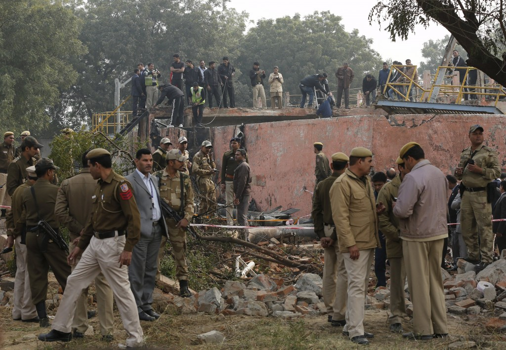 Security personnel stand next to the wreckage of a crashed aircraft on the outskirts of New Delhi, India, December 22, 2015. The aircraft crashed into a wall and burst into flames on the outskirts of the Indian capital, New Delhi, on Tuesday, killing all 10 people on board, officials said. REUTERS/Adnan Abidi