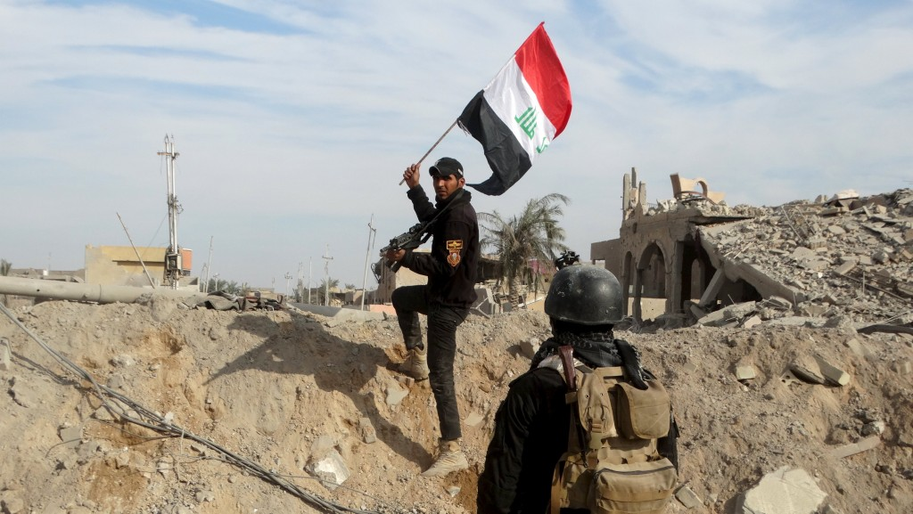 A member from the Iraqi security forces holds an Iraqi flag in the city of Ramadi, December 27, 2015. REUTERS/Stringer EDITORIAL USE ONLY. NO RESALES. NO ARCHIVE TPX IMAGES OF THE DAY