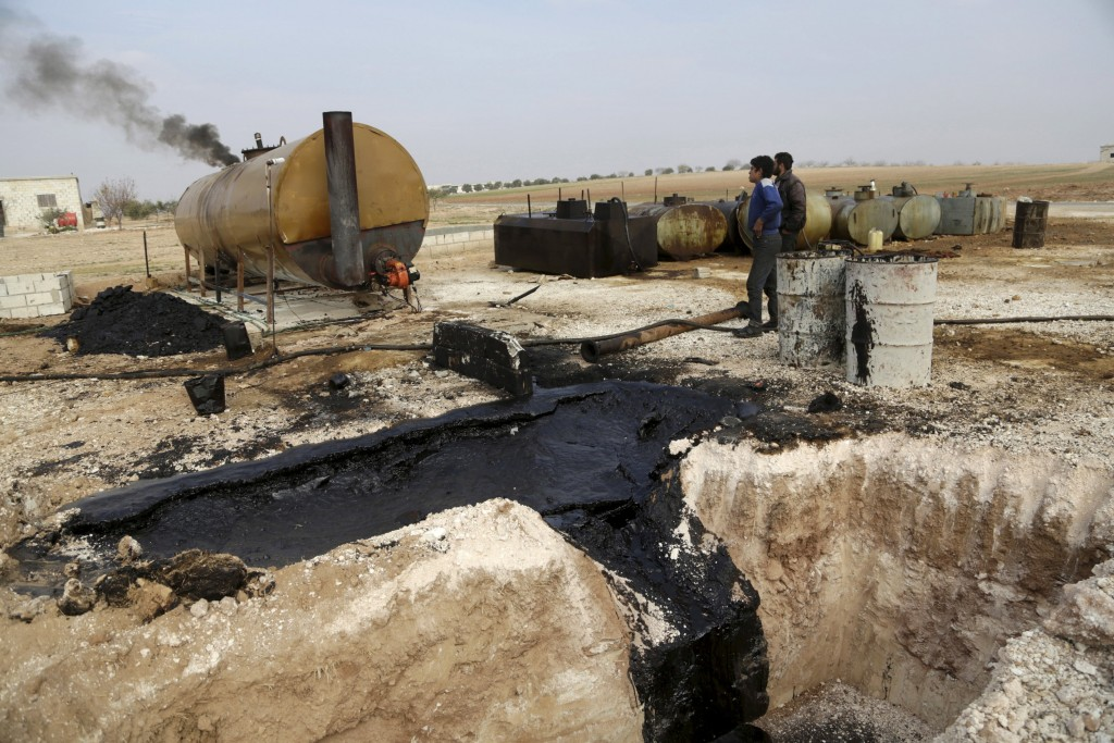 "Men work at a makeshift oil refinery site in Marchmarin town, southern countryside of Idlib, Syria in this December 16, 2015, file photo. The refinery site, owned by Yousef Ayoub, 34, has been active for 4 months. Ayoub says that he gets the crude oil from Islamic State-controlled areas in Deir al-Zor province and Iraq. Islamic State has set up departments to handle ""war spoils,"" including slaves, and the exploitation of natural resources such as oil, creating the trappings of government that enable it to manage large swaths of Syria and Iraq and other areas. REUTERS/Khalil Ashawi"
