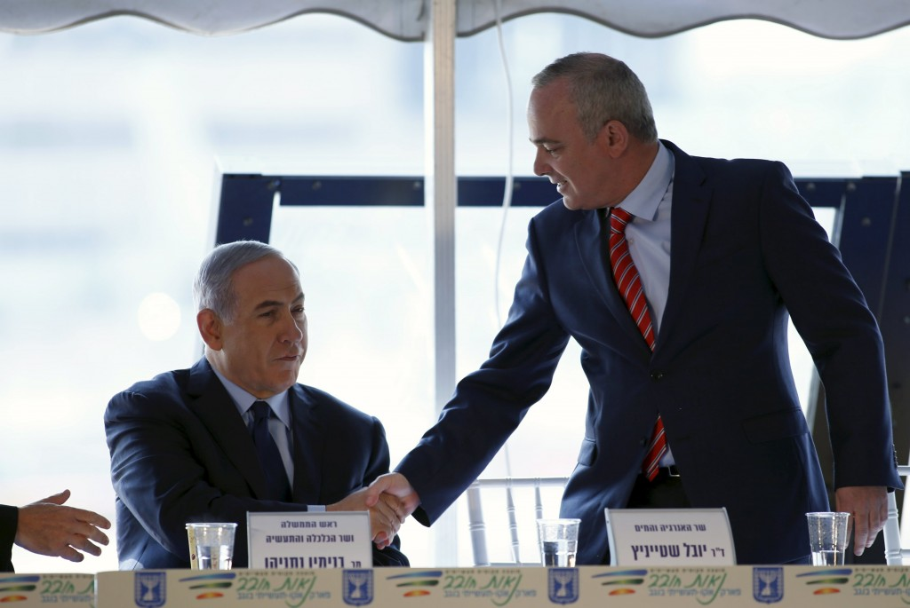 Israeli Prime Minister Benjamin Netanyahu (L) shakes hands with Energy and Infrastructure Minister Yuval Steinitz during a news conference where he announced his approval of Israel's natural gas deal, at the Neot Hovav Industrial Park near the southern city of Beersheba, Israel December 17, 2015. REUTERS/Amir Cohen