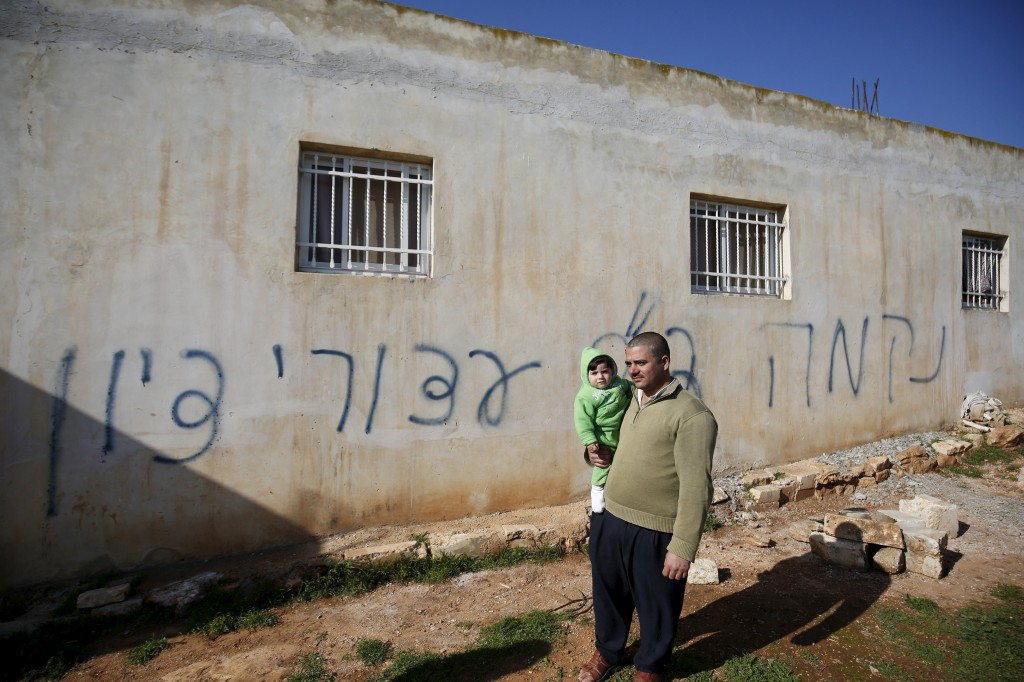 "A Palestinian man holds his son as he stands in front of Hebrew graffiti sprayed on the wall of a Palestinian home in what Israeli police believe was an attack by Jewish militants in the village of Beitillu near the West Bank city of Ramallah December 22, 2015. The Hebrew graffiti reads, ""Revenge"" and ""Hello from the detainees of Zion."" REUTERS/Mohamad Torokman"