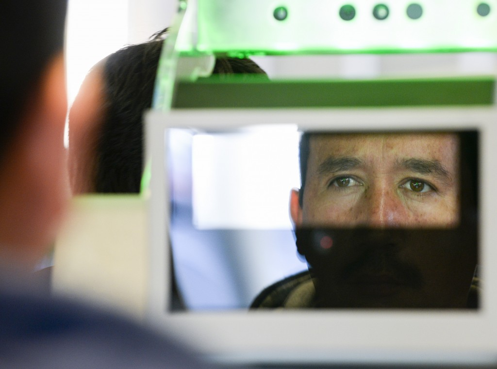 A pedestrian crossing from Mexico into the United States at the Otay Mesa Port of Entry has his facial features and eyes scanned at a biometric kiosk Thursday, Dec. 10, 2015, in San Diego.  (AP Photo/Denis Poroy)