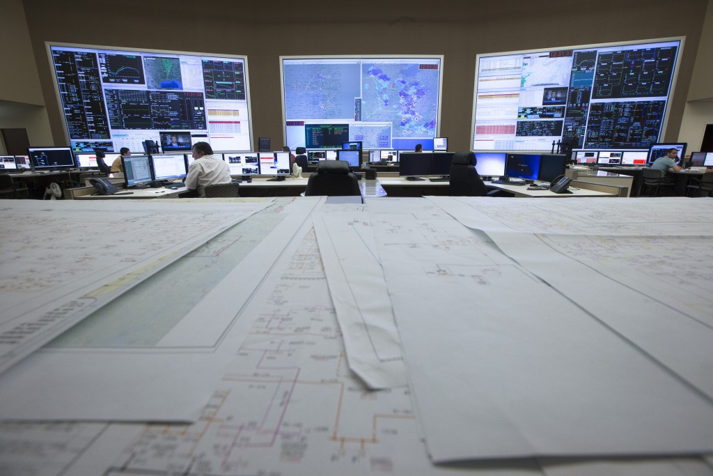 System control center operators work beneath giant monitors at an AEP Transmission Operations Center in New Albany, Ohio. (AP Photo/John Minchillo)