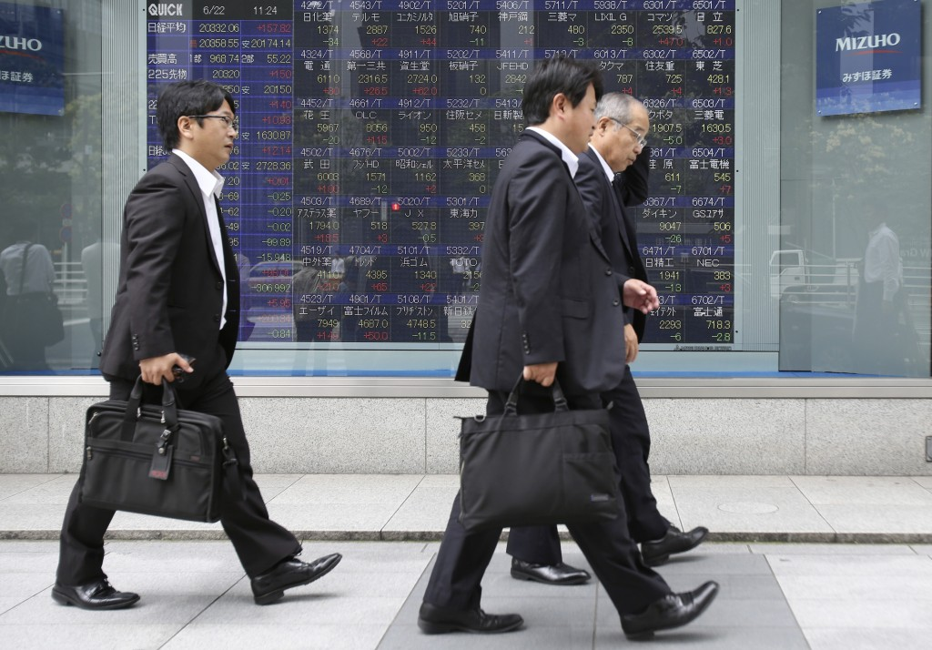People walk by an electronic stock board of a securities firm in Tokyo. (AP Photo/Koji Sasahara)