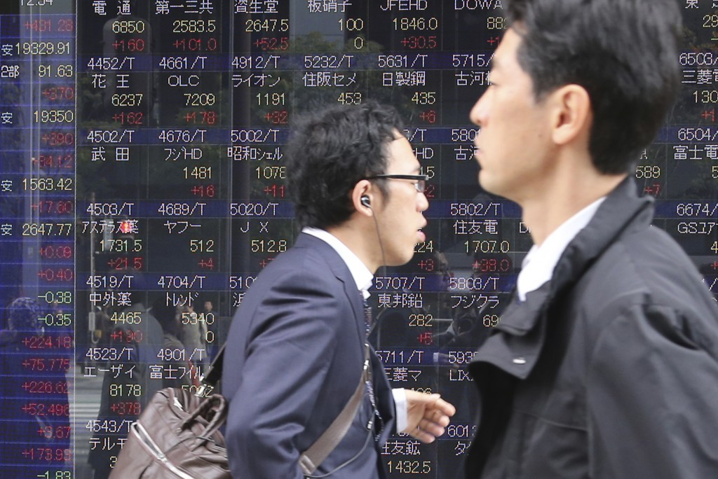 People walk by an electronic stock board of a securities firm in Tokyo, Thursday, Dec. 17, 2015. Asian stocks posted broad gains Thursday after the Federal Reserve ended protracted uncertainty in markets by raising interest rates for the first time in nearly a decade and signaling that further increases will be gradual. (AP Photo/Koji Sasahara)