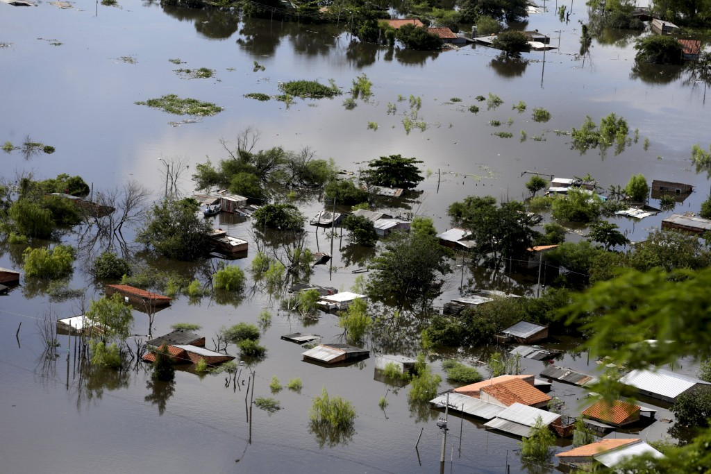 Houses are partially submerged in floodwaters in Asuncion, in this December 20, 2015 file photo. More than 100,000 people have had to evacuate from their homes in the bordering areas of Paraguay, Uruguay, Brazil and Argentina due to severe flooding in the wake of heavy summer rains brought on by El Nino, authorities said on December 26. In the worst affected country, Paraguay, around 90,000 people in the area around the capital city of Asuncion have been evacuated, the municipal Emergency Office said. Many are poor families living in precarious housing along the banks of the River Paraguay. REUTERS/Jorge Adorno/Files