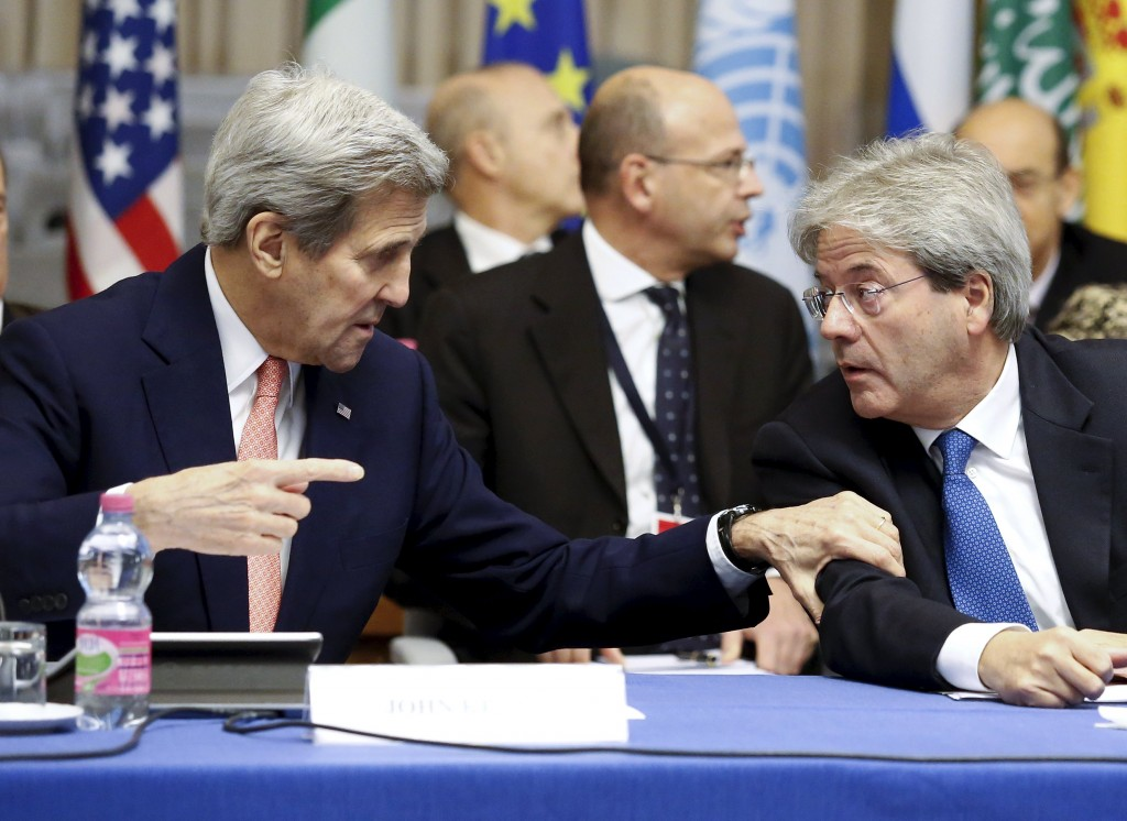 U.S. Secretary of State John Kerry (L) and Italian Foreign Minister Paolo Gentiloni talk during a meeting in Rome, Italy, December 13, 2015. After a year of U.N. talks to end Libya's conflict, Western powers are coaxing the warring factions closer to a deal they hope can help stop the spread of Islamic State militancy in the North African country. Kerry will co-chair the meeting of European, Middle Eastern and North African powers in Rome on Sunday to push the two camps to sign the U.N. proposal. REUTERS/Remo Casilli