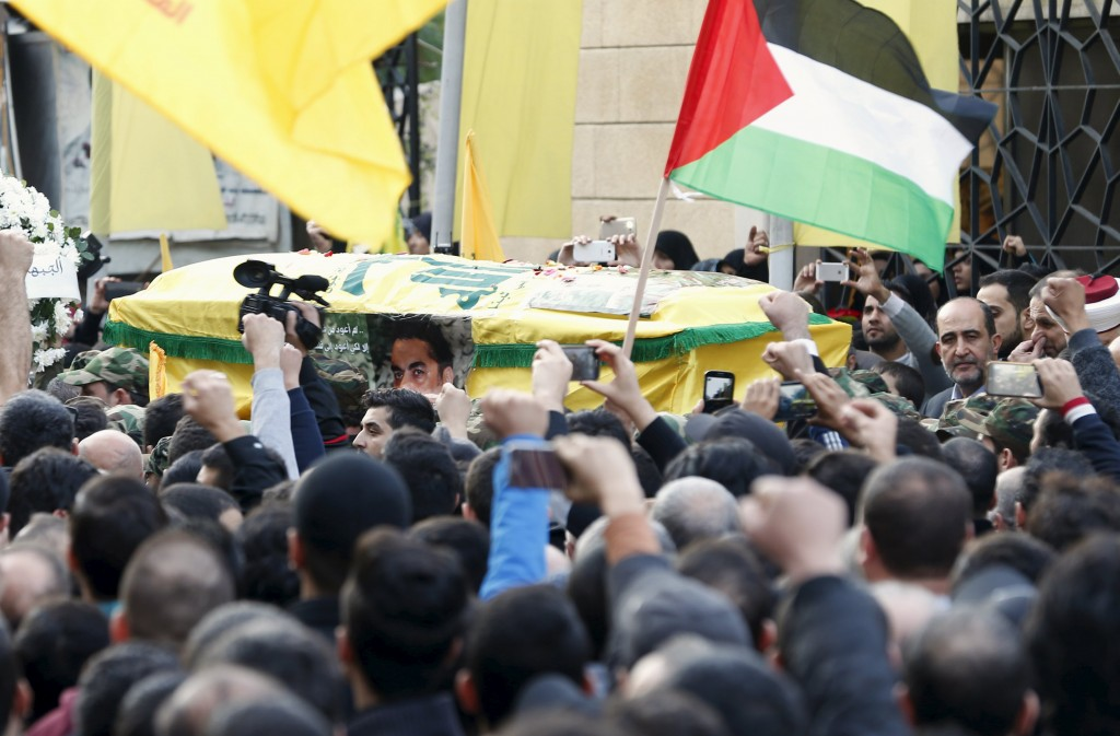 Hezbollah members carry the coffin of Lebanese Hezbollah militant leader Samir Qantar, as supporters carry Palestinian and Hezbollah flags during his funeral in Beirut's southern suburbs, Lebanon December 21, 2015. A Hezbollah official said on Monday that Israel will be held accountable for killing prominent militant Samir Qantar in a strike in Syria over the weekend. REUTERS/Jamal Saidi