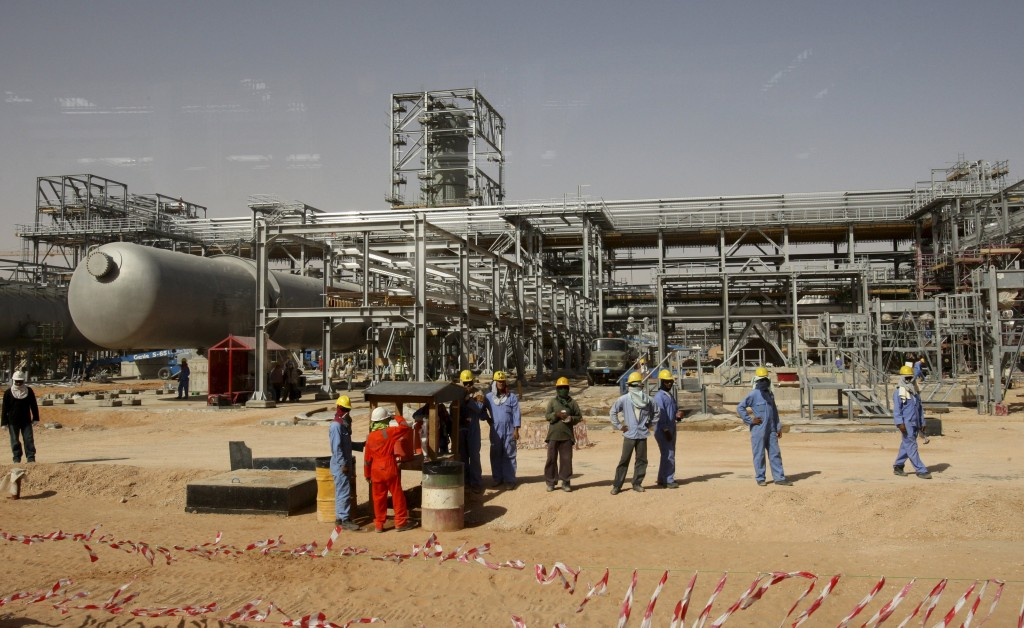 Workers look at journalists during a media tour of the Khurais oilfield, about 160 km (99 miles) from Riyadh, in this June 23, 2008 file photo. Saudi Arabia is shipping more crude oil to Asia over the last two months of 2015 as strong refining margins boost demand, trade sources said, helping the top oil exporter defend its market share amid fierce competition. To match MIDEAST-OIL/ REUTERS/Ali Jarekji/Files