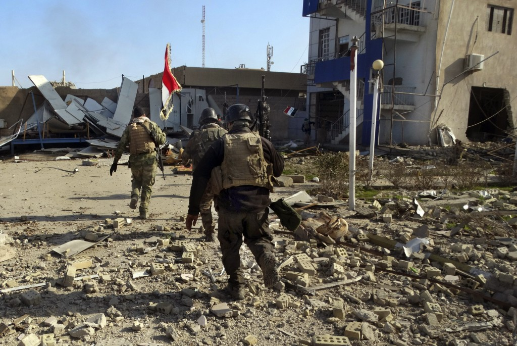 Iraqi security forces enter the government complex in central Ramadi, 70 miles (115 kilometers) west of Baghdad, Iraq, Monday, Dec. 28, 2015. Iraqi military forces on Monday retook a strategic government complex in the city of Ramadi from Islamic State militants who have occupied the city since May. (AP Photo/Osama Sami)
