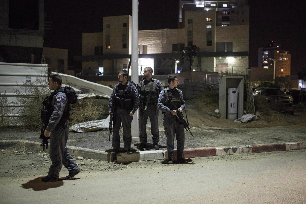 Israeli police stand guard in Kiryat Gat, Israel, Saturday Nov. 21, 2015. An assailant stabbed and wounded four Israelis, including a 13-year-old girl, in Kiryat Gat, on Saturday before fleeing the scene, setting off a large manhunt, police said. (AP Photo/Tsafrir Abayov)