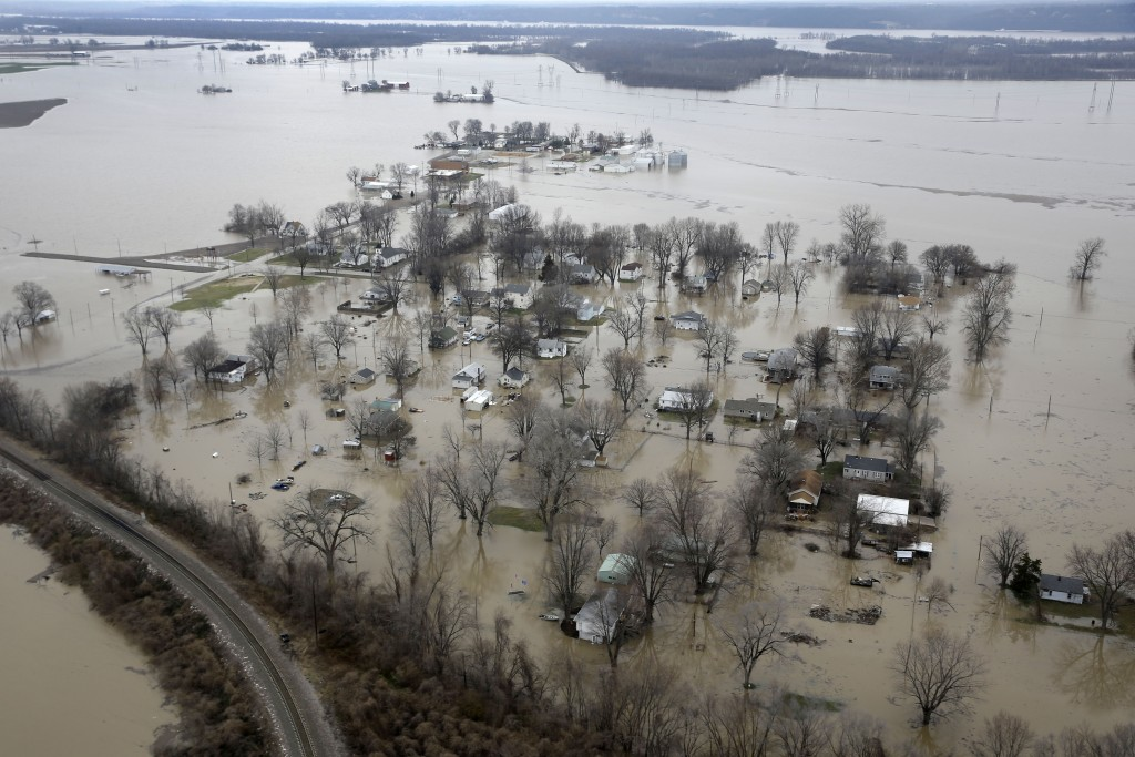 In this aerial photo, homes are surrounded by floodwater, Wednesday, Dec. 30, 2015, in West Alton, Mo. A rare winter flood threatened nearly two dozen federal levees in Missouri and Illinois on Wednesday as rivers rose, prompting evacuations in several places. (AP Photo/Jeff Roberson)