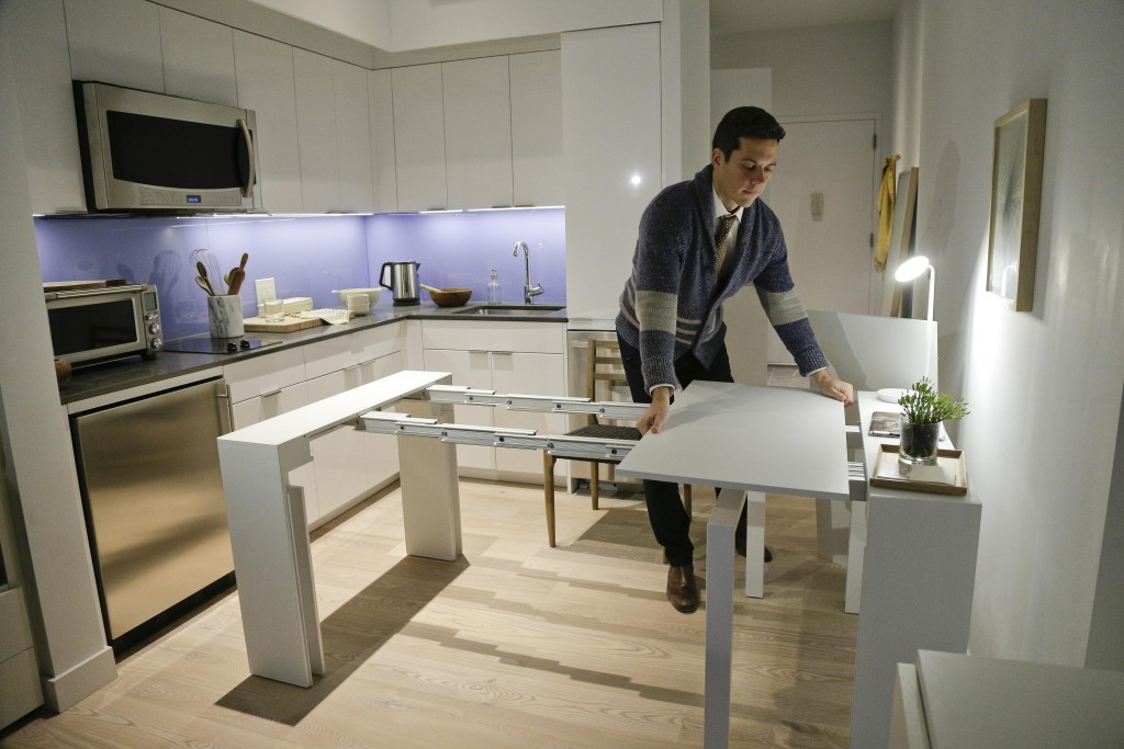 Stage 3 Properties co-founder Christopher Bledsoe demonstrates a desk that expands into a dining table that can seat up to 12 people inside one of the apartments at the Carmel Place building in New York. (AP Photo/Julie Jacobson)