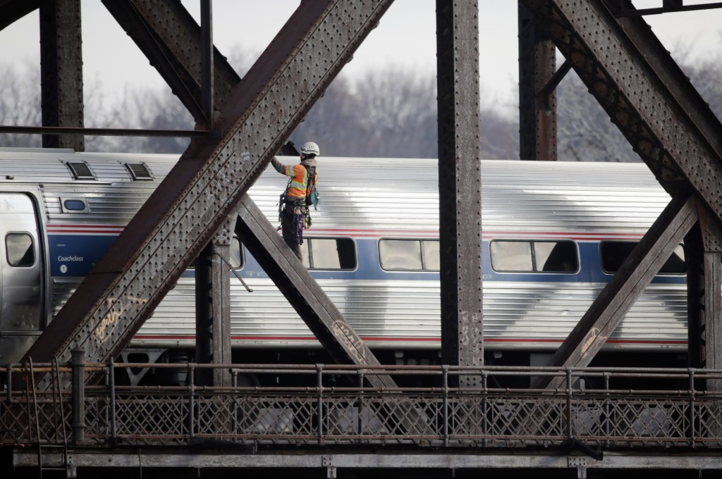 A man works on a rail bridge spanning the Hudson River as an Amtrak passenger train passes on Friday, Dec. 18, 2015, in Albany, N.Y. (AP Photo/Mike Groll)
