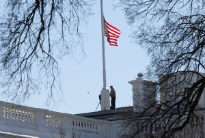 Workers lower the American flag above the White House on Thursday. (AP Photo/Pablo Martinez Monsivais)