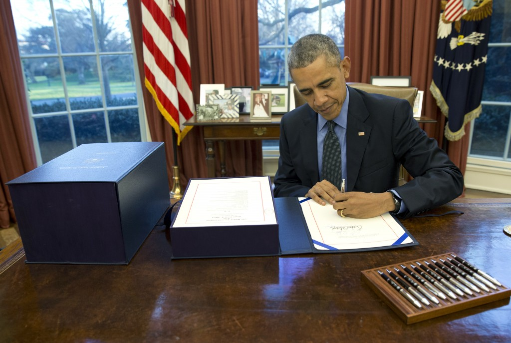 President Barack Obama signing the omnibus spending bill in the Oval Office on Friday. (AP Photo/Carolyn Kaster)