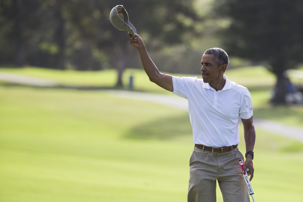 President Obama tips his hat to the crowd after finishing a round of golf at Mid-Pacific Country Club during his family vacation, in Kailua, Hawaii. (AP Photo/Evan Vucci)