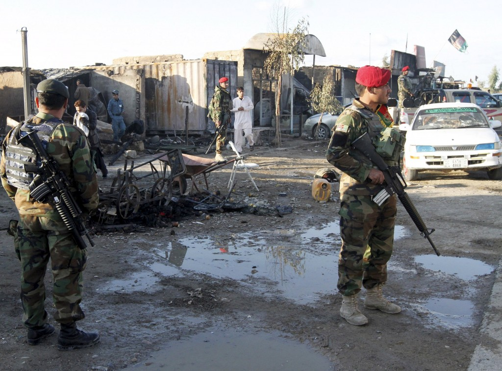 Afghan National Army (ANA) soldiers stand guard in front of a shop burned during the Taliban attack on Kandahar Airport. (Reuters/ Stringer)