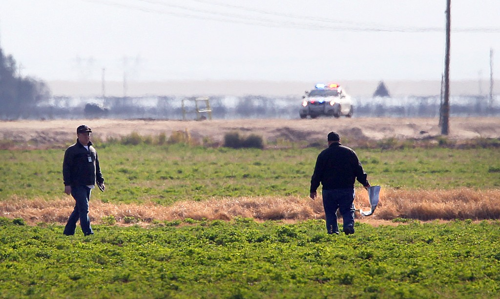 In this photo provided by the Bakersfield Californian, investigators search a field for debris from an aircraft crash in Bakersfield, Calif., Sunday, Dec. 20, 2015. Rescuers pulled multiple bodies from the wreckage of a small plane that crashed on Saturday into an orchard in central California after vanishing from radar, local and federal authorities said Sunday. (Henry A. Barrios/The Bakersfield Californian via AP)