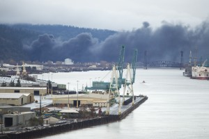Black smoke billows over the Willamette River in Portland, Or., near the St. Johns Bridge. (Stephanie Yao Long/The Oregonian via AP)