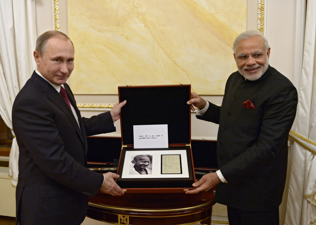 In this Dec. 23, 2015 photo, Russian President Vladimir Putin, left, and Indian Prime Minister Narendra Modi pose for a photo while exchanging official gifts during their meeting in the Kremlin in Moscow. (Alexei Nikolsky, Sputnik, Kremlin Pool Photo via AP)
