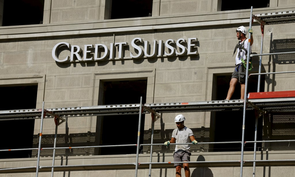 Construction workers stand on a scaffolding beside the logo of Swiss bank Credit Suisse at a construction site at the Bahnhofstrasse in this Zurich July 2, 2015 file photo. New Credit Suisse Chief Executive Tidjane Thiam will face the Swiss bank's vocal retail shareholders on November 19, 2015, when he will hope to avoid the mauling suffered by American predecessor Brady Dougan. Picture taken July 2, 2015. REUTERS/Arnd Wiegmann/Files