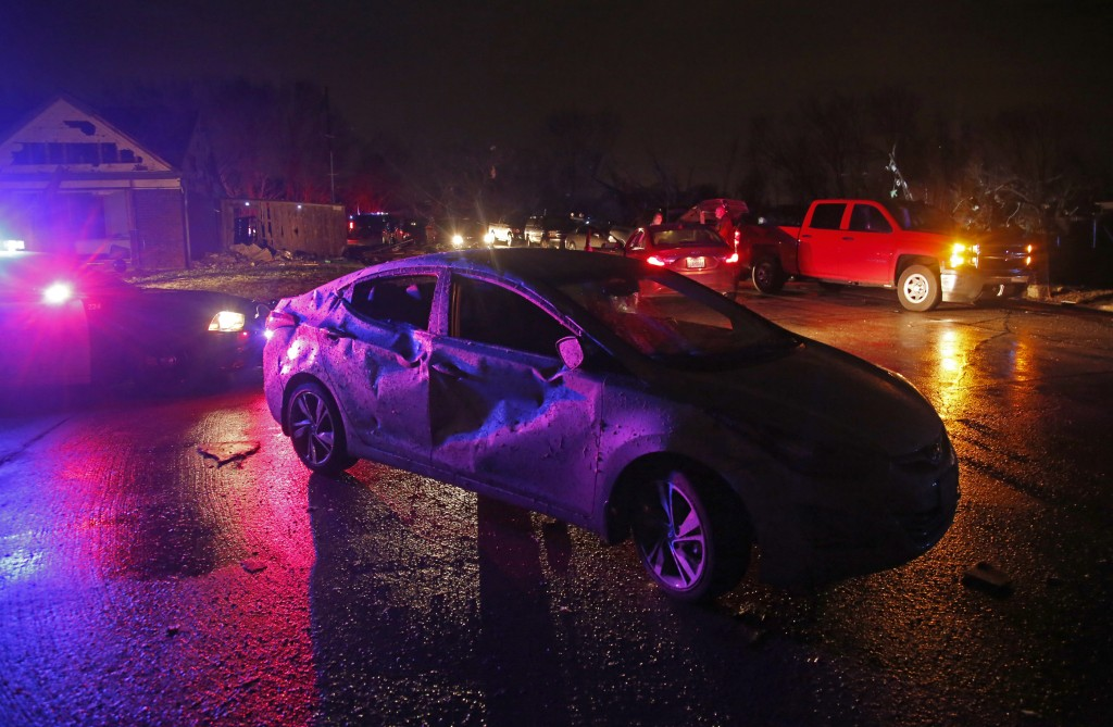 Police car lights illuminate Debbie Spruell's heavily damaged car after a tornado hit in Rowlett, Texas, Saturday, Dec. 26, 2015. Spurell was at home a few blocks away and not in the car at the time and was uninjured according to the The Dallas Morning News. Tornadoes swept through the Dallas area after dark on Saturday evening causing significant damage. (Guy Reynolds/The Dallas Morning News via AP) MANDATORY CREDIT; MAGS OUT; TV OUT; INTERNET USE BY AP MEMBERS ONLY; NO SALES