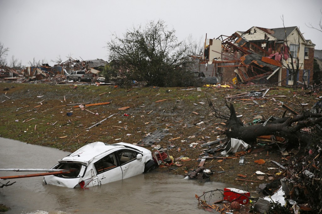 A car is flooded in a drainage ditch after Saturday's tornado on Schrade Road in Rowlett, Texas, Sunday, Dec. 27, 2015. At least 11 people died and dozens were injured in apparently strong tornadoes that swept through the Dallas area and caused substantial damage this weekend. (Nathan Hunsinger/The Dallas Morning News via AP)