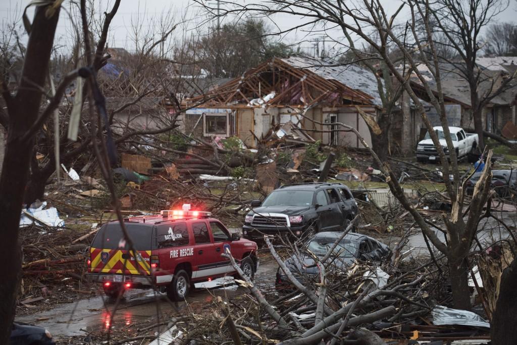 An emergency vehicle drives through a neighborhood in Rowlett, Texas, Sunday morning. (AP Photo/Rex C. Curry)