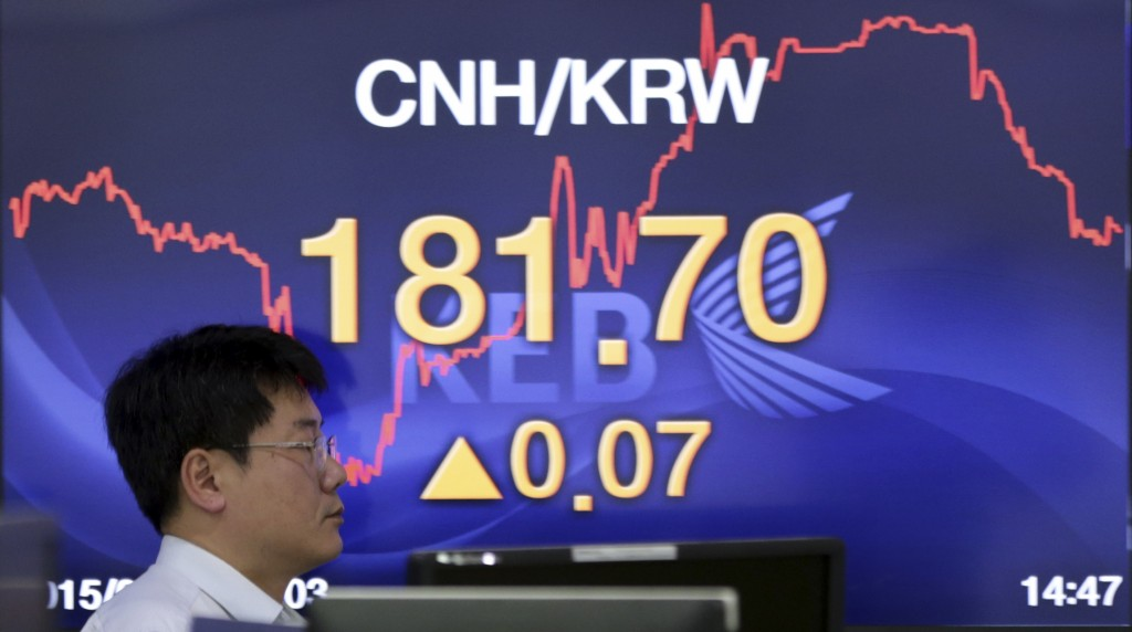 An employee walks by a screen showing the foreign exchange rate between the China and South Korea at a bank in Seoul, South Korea, Thursday, Aug. 13, 2015. Asian stock markets stabilized Thursday after a two-day sell-off sparked by China's currency devaluation. China's yuan fell again but the decline was smaller than before. (AP Photo/Lee Jin-man)