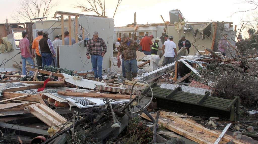 """People inspect a storm-damaged home in the Roundaway community near Clarksdale, Miss., Wednesday, Dec. 23, 2015. A storm system forecasters called """"particularly dangerous"""" killed multiple people as it swept across the country Wednesday. (Troy Catchings/The Press Register via AP) MANDATORY CREDIT"""