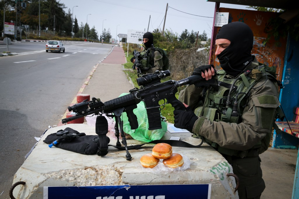 Israeli special forces soldiers stand guard near the Gush Etzion junction, where local residents provided them with sufganiyot. (Gershon Elinson/Flash90)