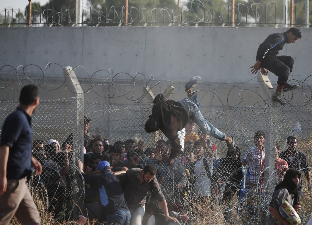 FILE - In this June 14, 2015, file photo, Syrian refugees cross into Turkey from Syria over and through a hole on the border fence in Akcakale, Sanliurfa province, southeastern Turkey. Marking a tragic milestone, the United Nations said in a statement on Thursday, July 9, 2015 that over 4 million Syrians have fled to other countries since the outbreak of civil war in their country more than four years ago. (AP Photo/Lefteris Pitarakis, File)