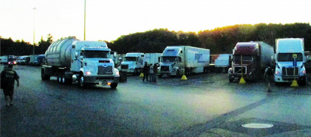 Trucks roll from a truck stop at dusk in Willington, Conn., last month. (AP Photo/Dave Collins)