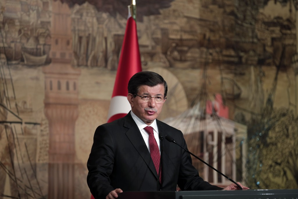 Turkish Prime Minister Ahmet Davutoglu talks during a joint news conference with Germany's Chancellor Angela Merkel, after their meeting at his office in Dolmabahce Palace in Istanbul, Sunday, Oct. 18, 2015. Merkel is meeting Turkish leaders to promote a EU plan that would offer aid and concessions to Turkey in exchange for measures to stem the mass movement of migrants across Europe's borders.(AP Photo/Lefteris Pitarakis)