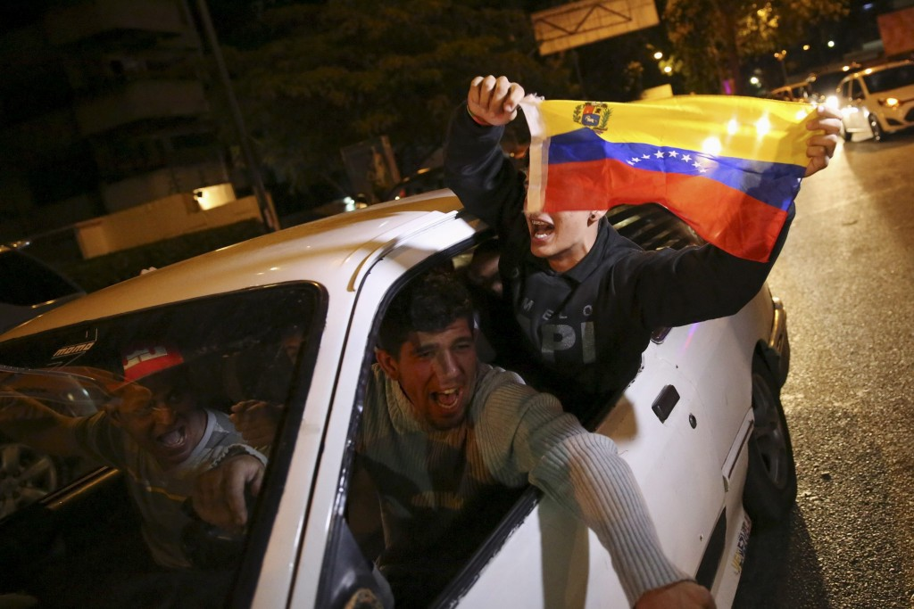 Supporters of the opposition Democratic Unity coalition wave a Venezuelan national flag from a car while they celebrate their victory on a street in Caracas December 7, 2015. Venezuela's opposition won control of the legislature from the ruling Socialists for the first time in 16 years on Sunday, giving them a long-sought platform to challenge President Nicolas Maduro. REUTERS/Nacho Doce