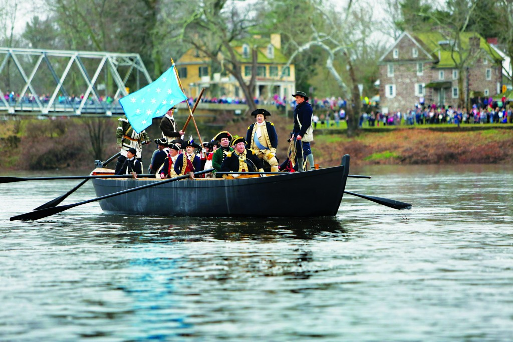 John Godzieba, standing second from right, portraying Gen. George Washington, on Friday looks towards New Jersey from a Durham boat during a re-enactment of the historic crossing of the Delaware River. (AP Photo/ Joseph Kaczmarek)