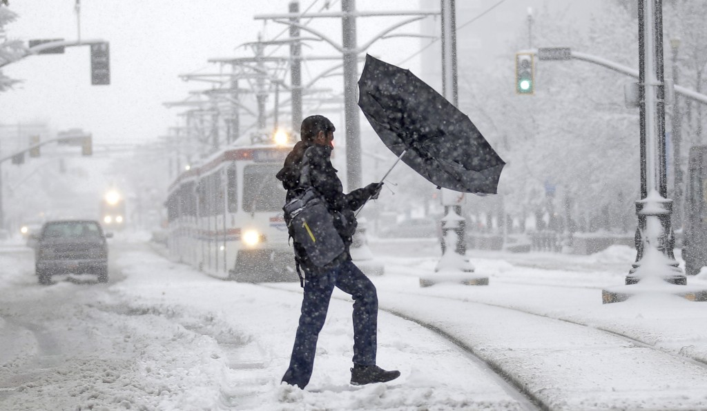 A man's umbrella blows inside out as he walks along downtown Salt Lake City Monday, Dec. 14, 2015. The first major winter storm of the season dumped up to a foot of snow in some parts of the Salt Lake City metro area, snarling traffic on morning commutes to work and school. (AP Photo/Rick Bowmer)