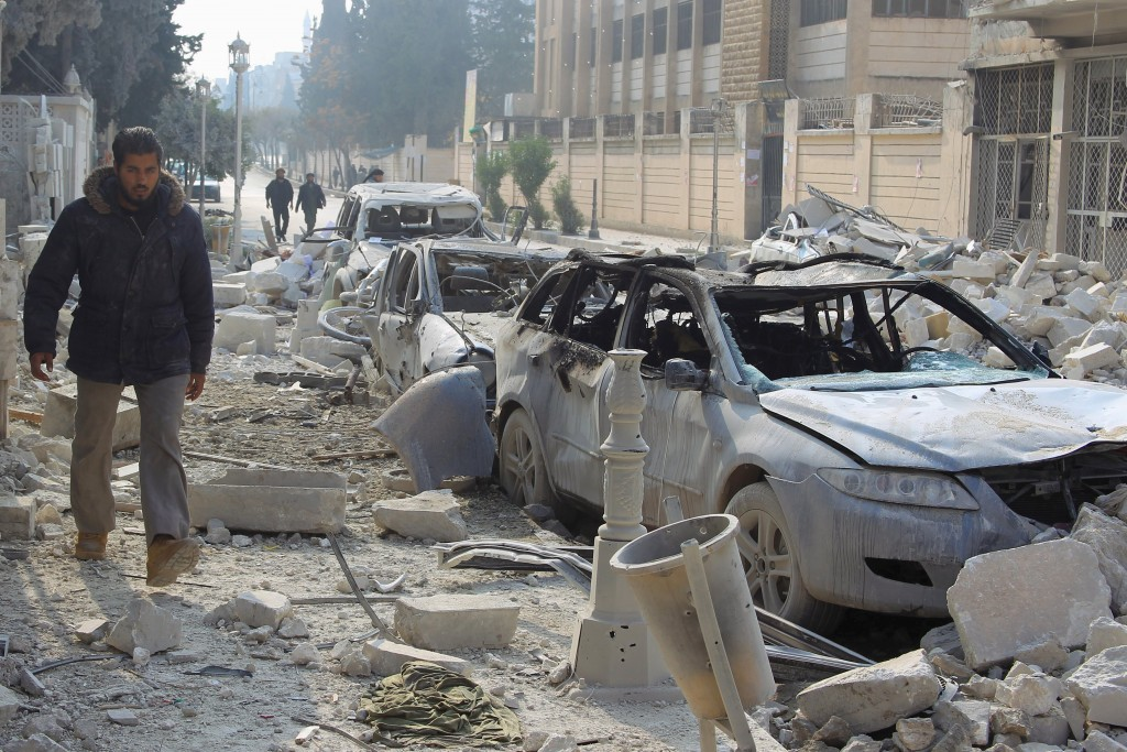 A man walks past damaged cars at a site hit by what activists said were airstrikes carried out by the Russian air force in Idlib, Syria, on Sunday. (Reuters/Ammar Abdullah)